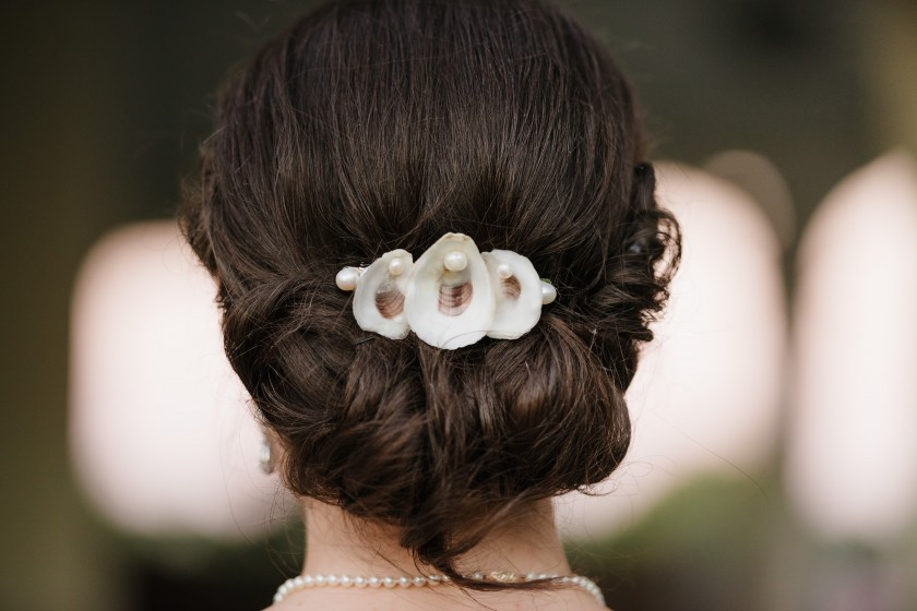 The bride's mother handcrafted several tabletop decorations from oyster shells, and even incorporated them into her daughter's upswept 'do – a keepsake they will treasure always.